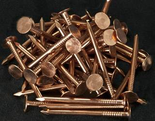 Several Smooth Shank Copper Roofing Nails In The Black Background